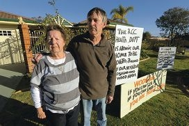 Bev and Roy Strong have erected signs outside their house criticising the City for what they say is inaction against a neighbour's 'toxic' chimney smoke. Picture: Jon Hewson d403785d