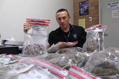 An officer with some of the drugs found at various homes in the southeastern suburbs.