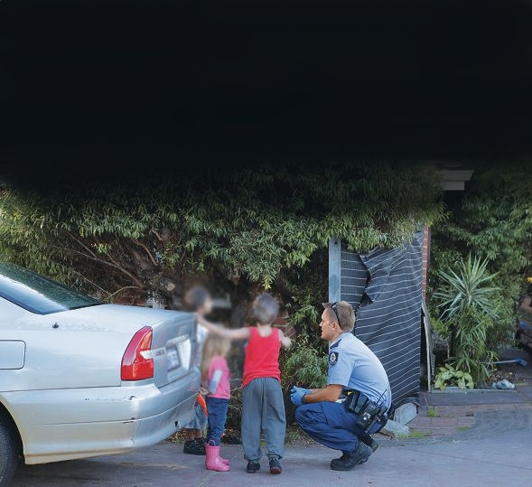 A police officer talks to some children at the scene of a house raid last week.