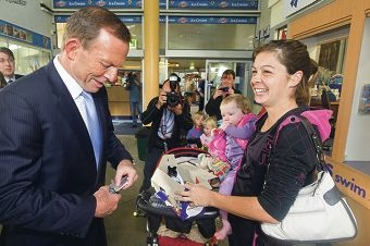 Tony Abbott buys a chocolate bar from Natasha Laughton. Picture: Jon Hewson d404029