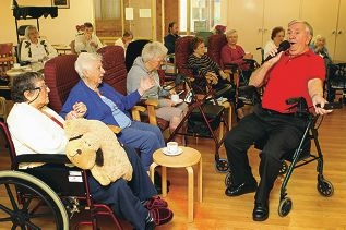 Volunteer Gary Heatley (71) in a sing-a-long with hostel residents.