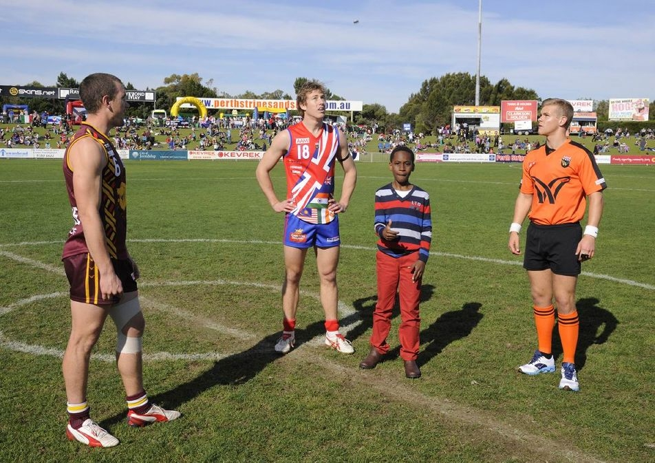 Abiola Oyenaike tosses the coin in the presence of umpire Nathan Williamson, West Perth captain Jay van Berlo and Subiaco skipper Kyal Horsley. Picture: Chris Kershaw