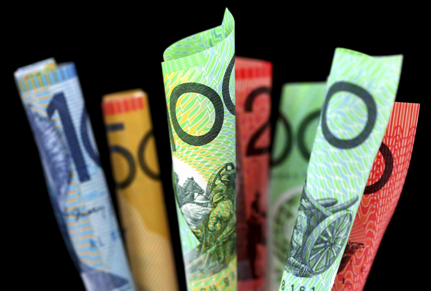 Australian money ~ furled Australian notes, with black background.  Focus on front $100 note.