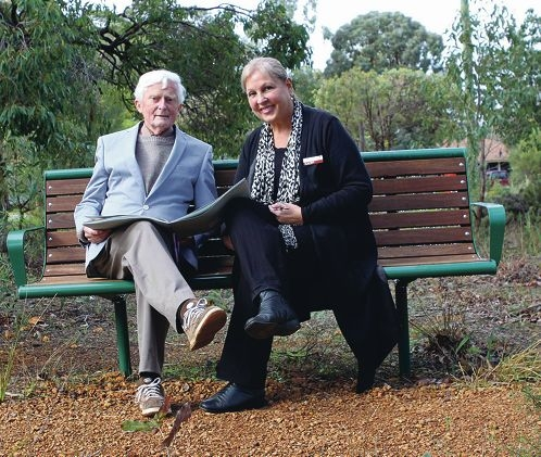 Barrie Oldfield and Shire of Kalamunda president Sue Bilich enjoying a collection of his photographs on the new park bench at Willoughby Park. Picture: Julian Wright