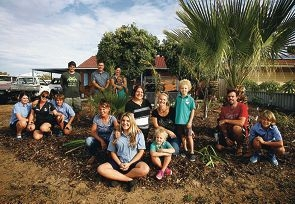 Tina Guariglia, at centre, with friends and family members, outside her newly renovated Golden Bay home. Picture: Marie Nirme www.communitypix.com.au d418264