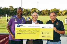 Perth Glory soccer star William Gallas and ME Bank WA state manager Drew Healey, presenting Forrestfield United Soccer Club president Carlos Mendes with a cheque for $1000.