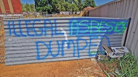 A hastily made sign warns of the danger of deadly asbestos dumped at a local property recently.