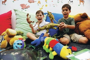 Speech and language at play: Micah enjoys a dinosaur game with his older brother Jesse.