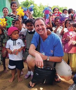 Gary Hewett surrounded by children in Cambodia.