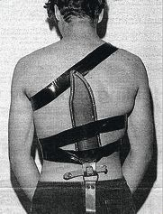 A police photograph of the murderer with the knife sheath strapped to his back.
