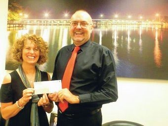 Sue Gillam is handed the cheque byNigel Haines.