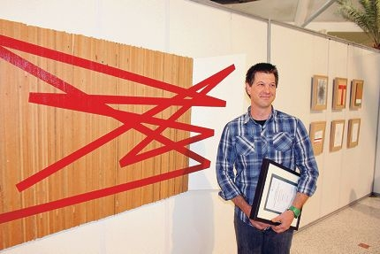 Mark Parfitt stands alongside his award-winning artwork entitled Return Game, comprising the larger main work in red and several framed 'journal' entries pictured right. Picture: Justin Bianchini