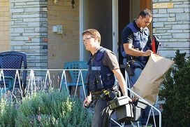 Police seize items including drugs and cash during the property search.