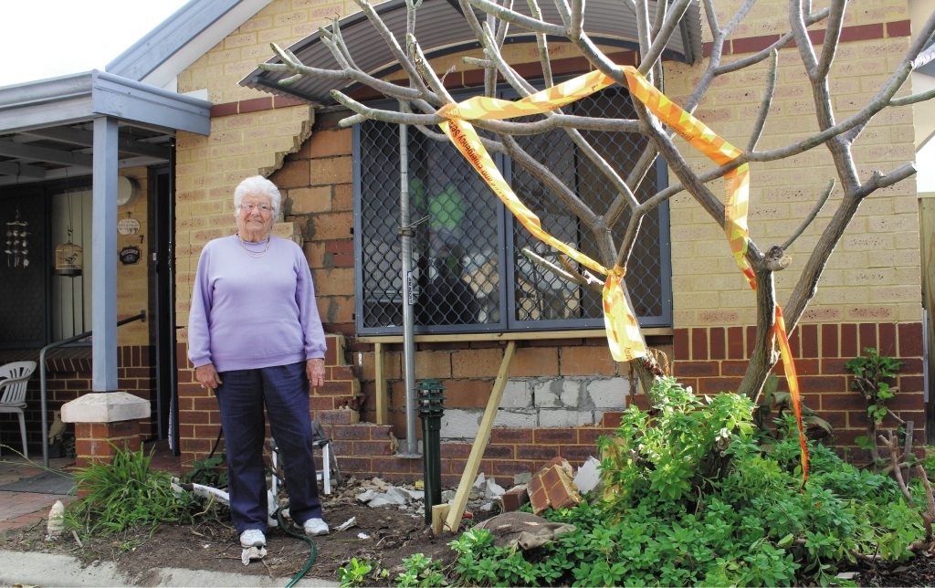 Joy French poses next to the wall and window, which have undergone repairs after a 4WD vehicle reversed through it.