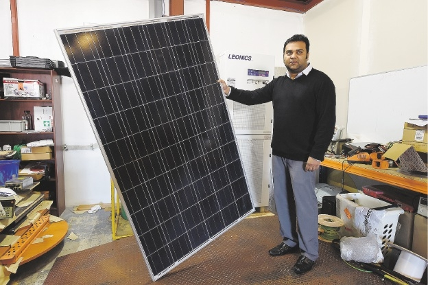 Business analyst Nikhil Jayaraj with a solar panel.Picture: Jon Hewson         www.communitypix.com.au   d439040