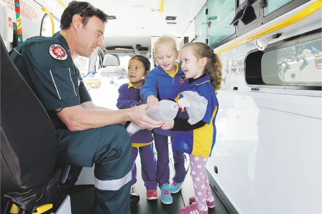 Paramedic Nik Stewart with kindy students Serenity Vann,Tashani Morrocco and Shayla Mander. Picture: Marcelo Palacios d438426