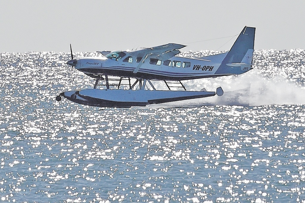 A Perth Seaplanes Catalina Adventures seaplane flies over the ocean.