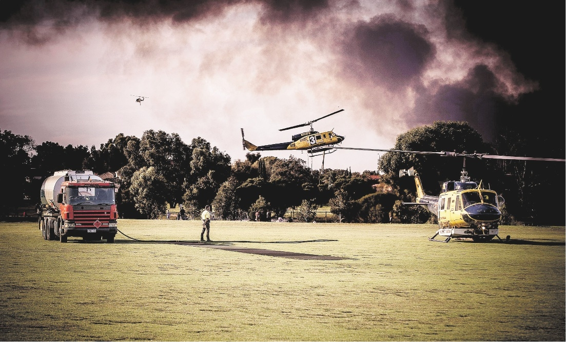 Helicopters battling the Gnangara plantation fire filling up at Warradale Park in Landsdale. Picture: Josh Tucker.