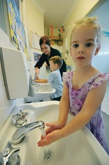 Abi Davis (3) washes up, while day carer Jess Breasley helps Jacob Stanesby (3). Picture: Jon Hewson d406564