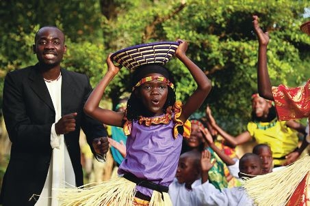 Ronnie Kabwama, one of the 10 adults who travel with the choir, and Imelda Namayanja perform with the Watoto Children's Choir.