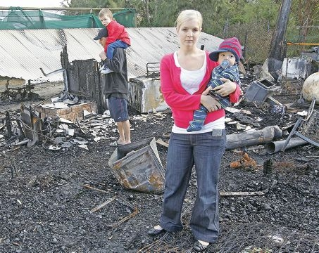 West Swan couple Sarah Brodie and Daniel Paterson, and their sons Brayden and Rylee, inspect their fire-ravaged home.