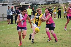 Kira Phillips chases the ball while team-mate Celina Seymour blocks an opposition player.