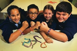 Students Calixia Lovo (12), Montel Vieyka (9), Georgia Gill (8) and Jonathon Tartaglia (11) with bracelets sent to them by the detainees.d398533