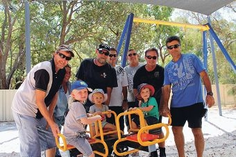 The crew from Wagerup refinery and some children enjoying a ride around the newly installed four-way see-saw.