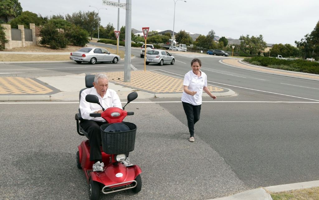Kinross petitioner Mary O'Byrne helps Len Thompson cross Marmion Avenue. Picture: Martin Kennealey d447392