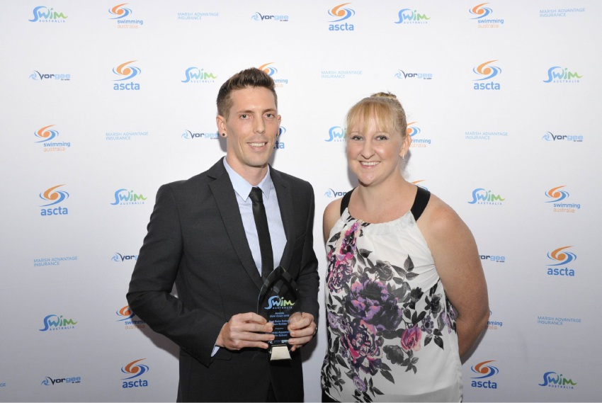 Swim school co-ordinator Lee Duffy accepting the award from Olympic gold medallist  Jessicah Schipper.