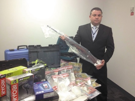 Detective Sergeant Craig Stephen with the seized drugs, stolen electrical items, $103,000 in cash and a stolen gun. Picture: Jesse Morganti