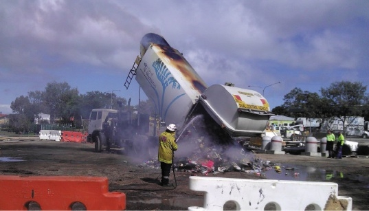 A firefighter cools the |rubbish as it is dumped.