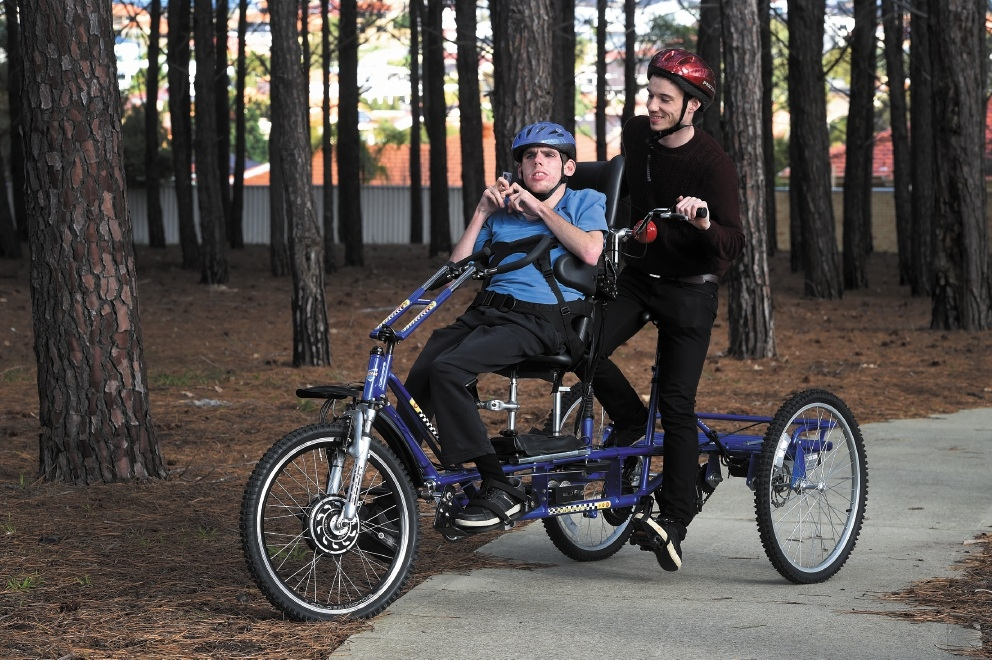 Eamon Guilfoile on his bike with support worker Ben Slater.Picture: Jon Hewson           d442002