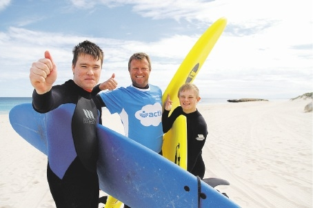 Taj Burrow (centre) offers surfing tips to Activ  clients Matthew Caple and Daniel Kirk at Trigg beach. Picture: Tom Rabe
