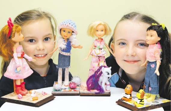 Year 2 students Grace Millett and Emilynne Lawton with some of the dolls created by Amira Romanowski. Picture: Martin Kennealey d441838
