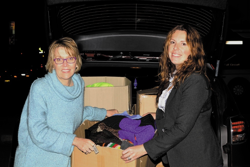Michelle Dunlop and Ruth Marshall with a box of clothes for Perth's homeless.