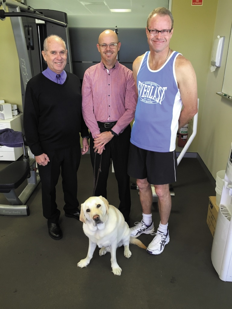 Ian Braimbridge (right) with his guide Tony Hagan (middle), vision impaired teammate Rupert Emanuel (left) and guide dog Gidgee.