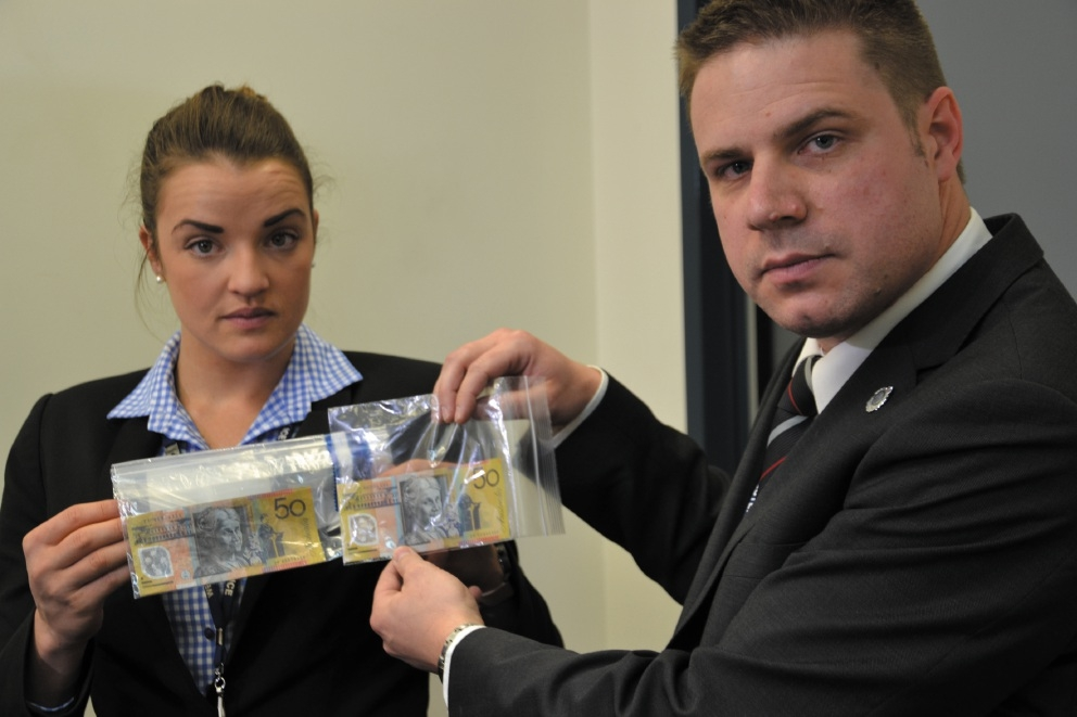 Det Sgt Matt Surman holds a legitimate $50 note, while Det Snr Const Trisha Lake holds up some of the counterfeit $50 notes. Pictures: Tim Mayne