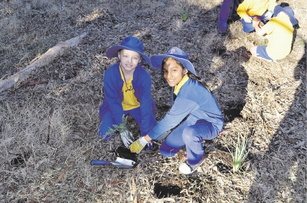 Gosnells Primary School Year 5 students Shelby James and Kalpna Panchal plant trees at Mary Carroll Park.