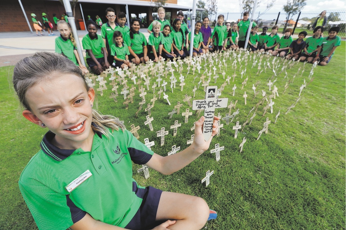 Courtney-Ann Tassell holds one of the crosses with her school mates in the background. Picture: Bruce Hunt        www.communitypix.com.au   d435918