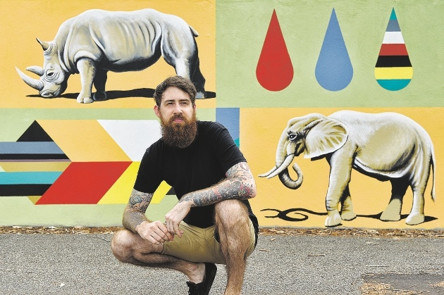 Brenton See in front of his animal canvas painted on the wall of Fresh Provisions.