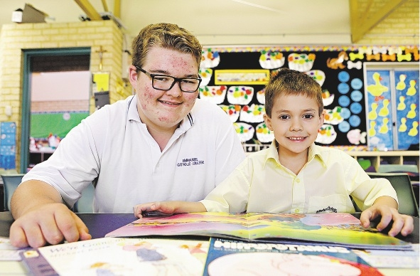 Emmanuel Catholic College Year 9 student Curtis Watts reads with Mater Christi Catholic Primary School Year 1 student Tanha Bebek.
