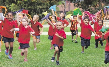 Some pre-primary and Year 1 students running with their Harmony Day kites.  Picture: Martin Kennealey