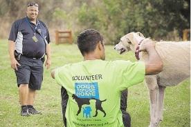 Reintegration officer Roger Jantjies with a prisoner and a refuge dog.