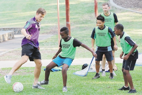Perth Glory player Chris Harold with Save the Children program participants. Picture: Marcelo Palacios                          d434613