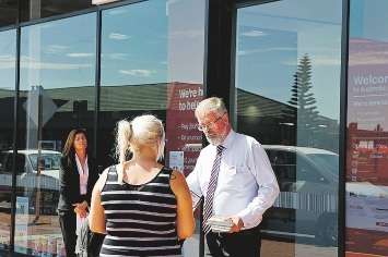 Australia Post network planning manager Steve Ryan talks to a customer outside the Clarkson store.