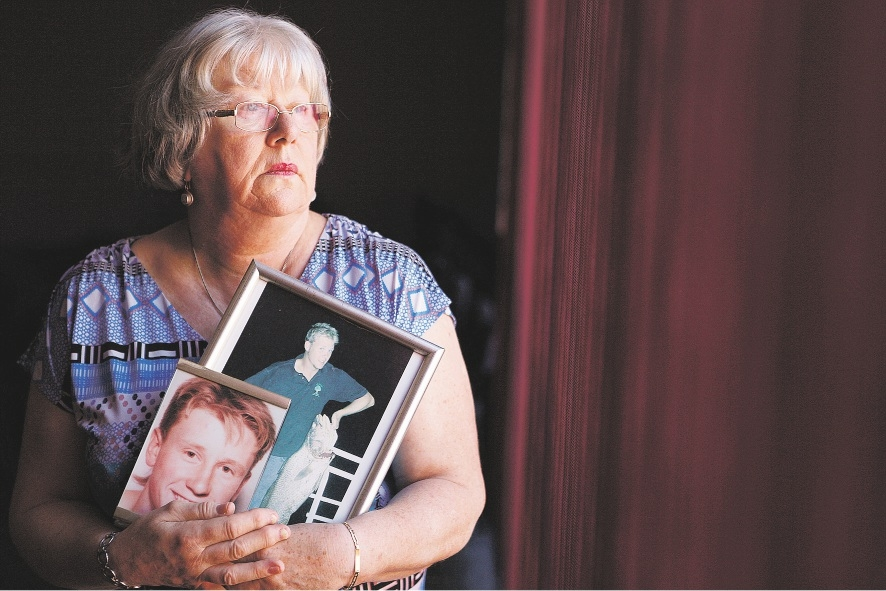 A path through the pain: Alison Flanagan, holding pictures of the two sons she lost to suicide, turned to Compassionate Friends and said it saved her life. She is now the president of the group.