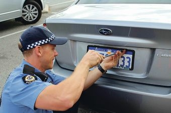 A police officer fitting anti-theft screws to a shopper's car.