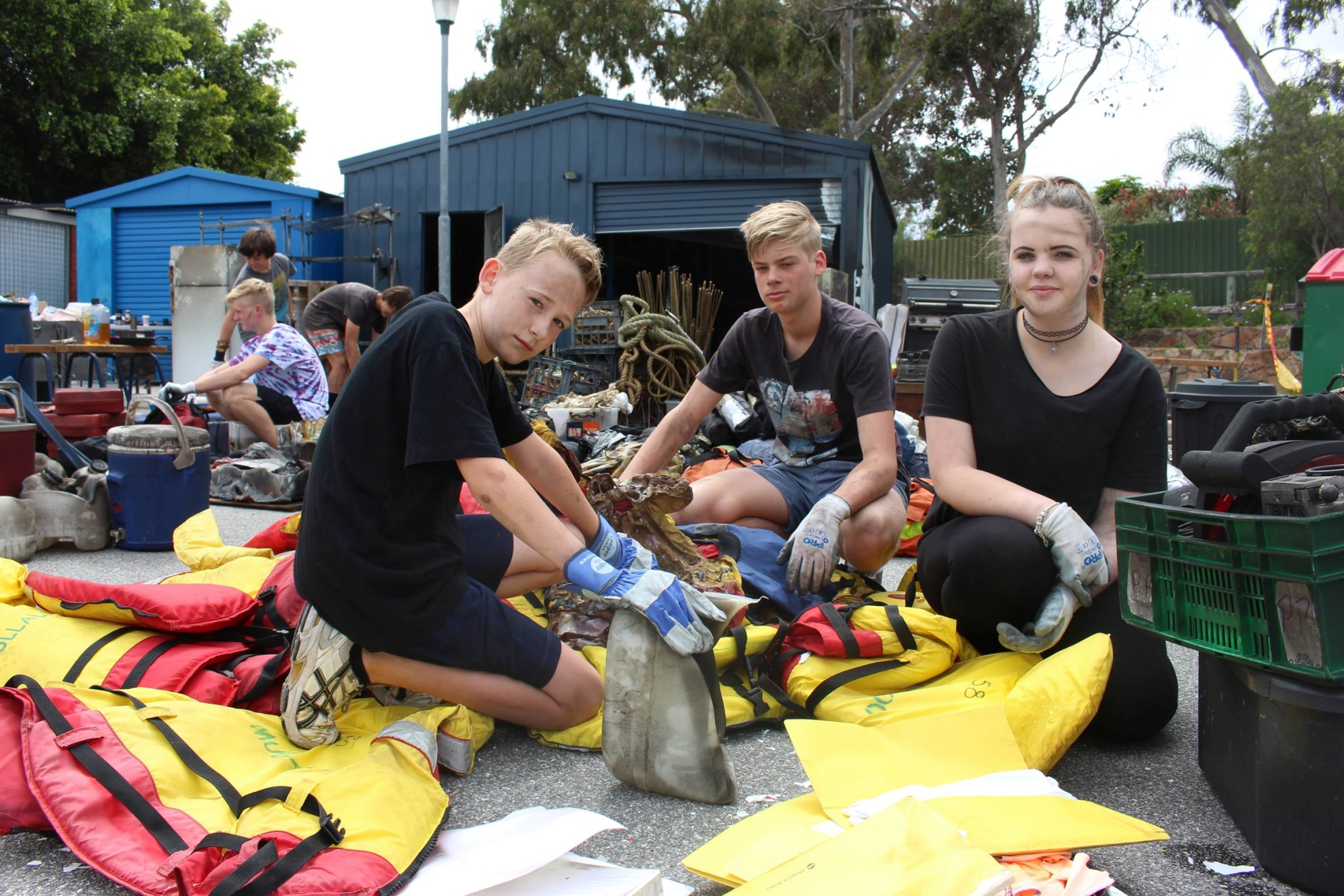Angry, annoyed: Jacob Evans, Brendan Keilar and Holly Calacob take part in the clean-up after the arson attack.