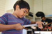 Trevor Ryan (9) takes part in a woodworking workshop. Picture: Martin Kennealeyd426974